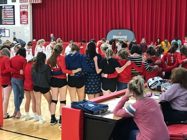 What really matters? Opposing volleyball teams uniting in prayer for a fan with a medical emergency.